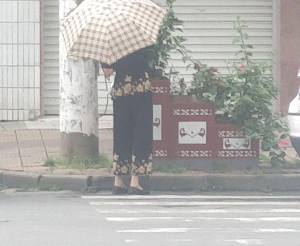 因为打着伞,看不到正面。